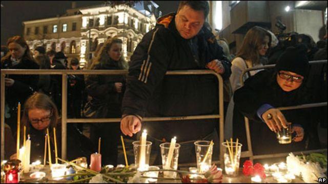 Люди зажигают свечи в память о жертвах взрывов