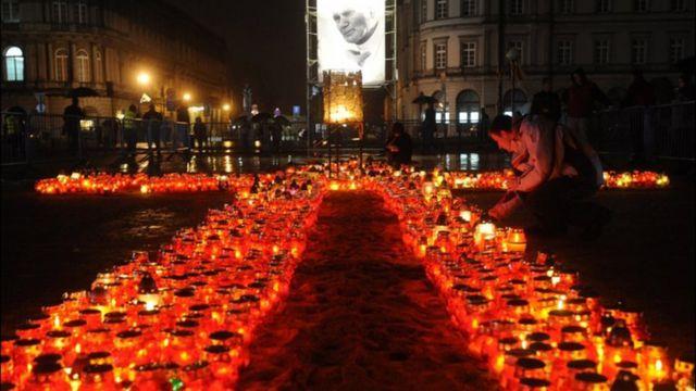 شاب بولندي يوقد شمعة بجانب صورة البابا الراحل يوحنا بولس الثاني في وارسو