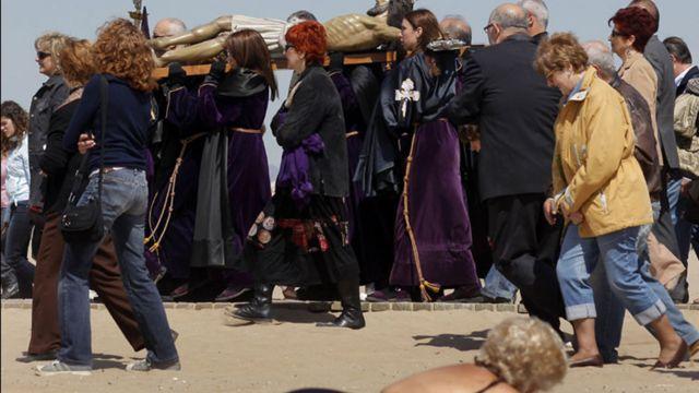 سيدة تستمتع باشعة الشمس في مدينة فالنسية الاسبانية بينما يحمل مؤمنون تمثالا للمسيح في مسيرة على طول الشاطئ