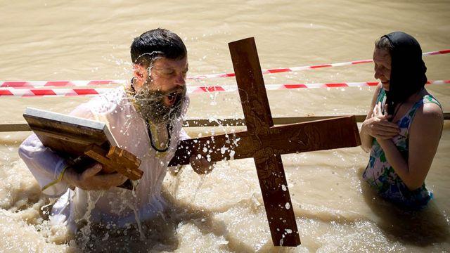 قس ارثوذكسي يغطس في نهر الاردن قرب قصر اليهود في اريحا