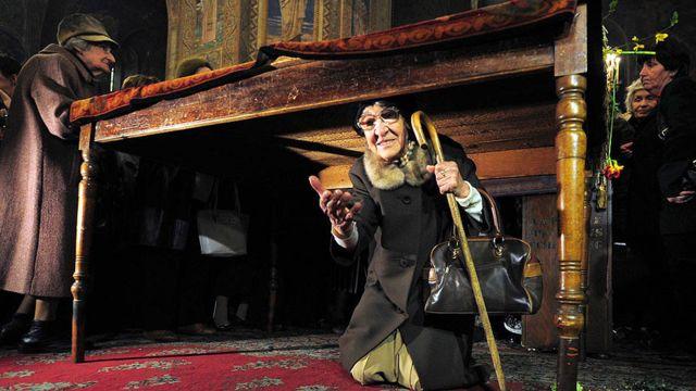 سيدة تمر تحت طاولة وضع عليها انجيل في احدى كنائس صوفيا ببلغاريا