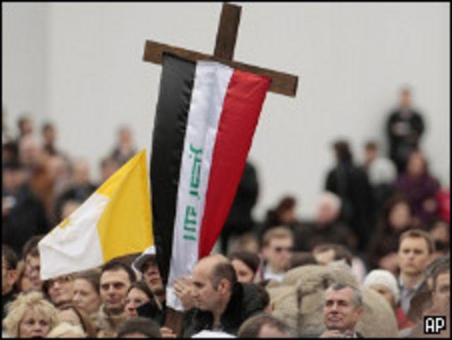 عراقي يرفع صليبا عليه العلم العراقي امام البابا
