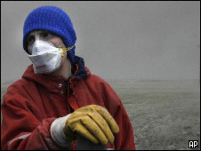 مربي ماشية ايسلندي يرتدي قناعا للوقاية من سحب رماد بركاني