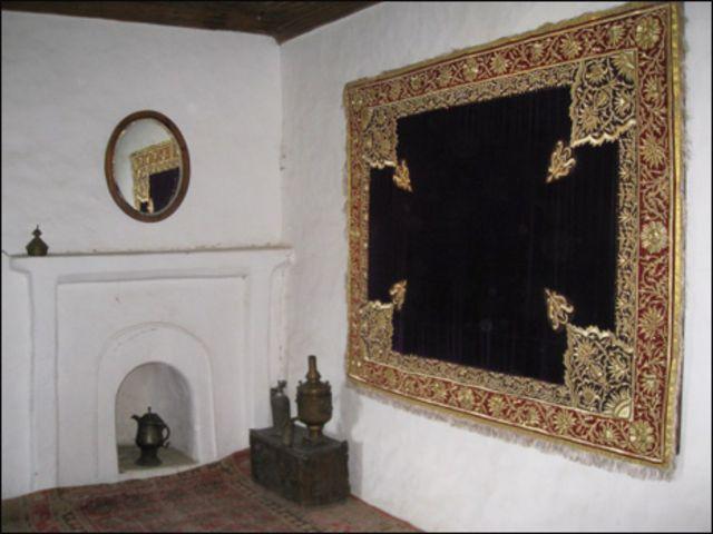 قلعے کے ایک کمرے کا منظر جہاں دیوار پر مقامی طور پر تیار کردہ قالین لٹکا ہوا نظر آ رہا ہے