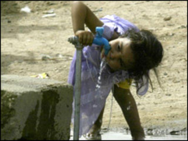 Niña bebiendo agua en un campo de refugiados de Irak.