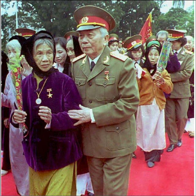 """Vị tướng đi cùng một """"Bà mẹ Việt Nam anh hùng"""" tại buổi lễ ngày 19/12/1994 vinh danh những bà mẹ có người thân hy sinh cho chính phủ cộng sản trong cuộc chiến chống Pháp và Mỹ."""