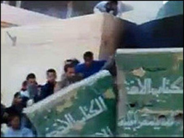 利比亞圖卜魯格示威者推翻卡扎菲《綠皮書》的塑像(17/2/2011)