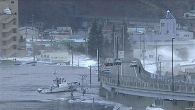 قارب تدفعه امواج التسونامي للاصطدام بأحد الجسور في مدينة كامايشي 11/3/2011