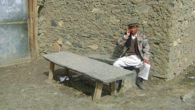 مردی شغنانانی در پشت میز سنگی با تلفن صحبت میکند