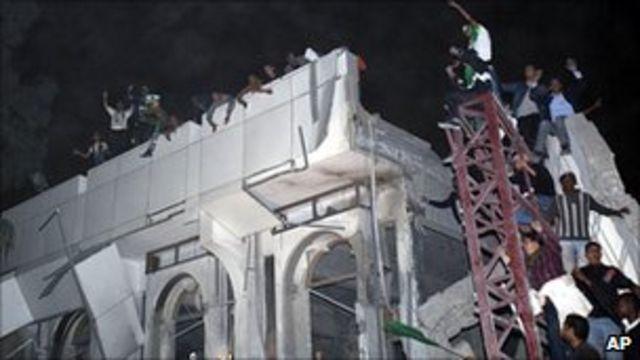 卡扎菲支持者在的黎波里被炸毀的建築物上喊口號(25/4/2011)