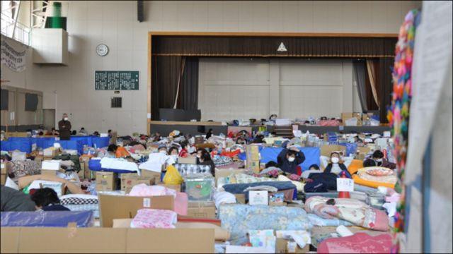Trước 8 giờ sáng, chúng tôi đến Trung tâm lánh nạn Trường Trung học phổ thông Watari. Nơi đây có 650 người sơ tán. Cuộc sống ở Trung tâm còn thiếu thốn đủ thứ. Có người gặp chúng tôi hỏi xin chăn vì không đủ ấm. Rất tiếc là chúng tôi đã không nghĩ đến tình huống này.
