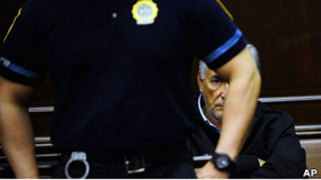 Полицейский стоит перед Домиником Стросс-Каном