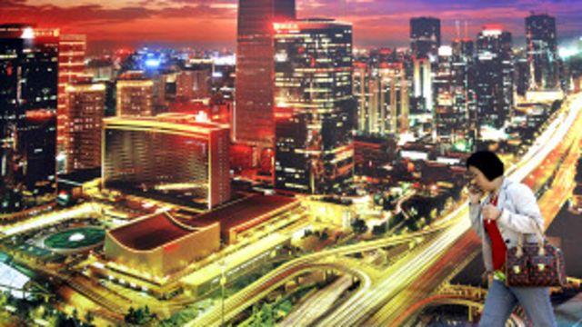 北京街頭民眾走過一幅以中心商業區夜景為題的巨型廣告(資料圖片)