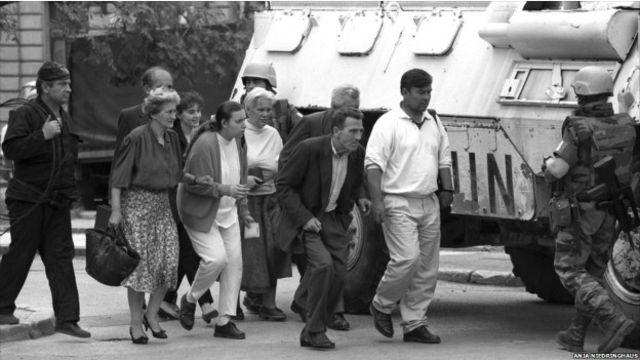 Warga Sarajevo melewati panser pasukan PBB di Sarajevo yang dikepung rapat oleh pasukan Serbia.
