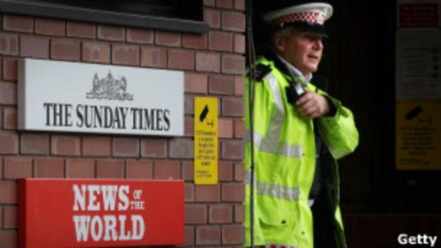 Policial caminha pela sede da News Association.