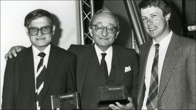 """د بي بي سي پښتو خپرونې په ۱۹۸۸ کال کې په خپل روغتيايي پروګرام """"روغه څټه"""" سره د سوني راډيو """"د ټولنې غوره خدمت پروګرام"""" جايزه وګټله. په انځور کې له کيڼ نه ښي لور ته د دغه پروګرام جوړونکی ګوهر رحمان ګوهر، يو بل ګټونکی او د پښتو څانګې مشر ګورډن اډم"""