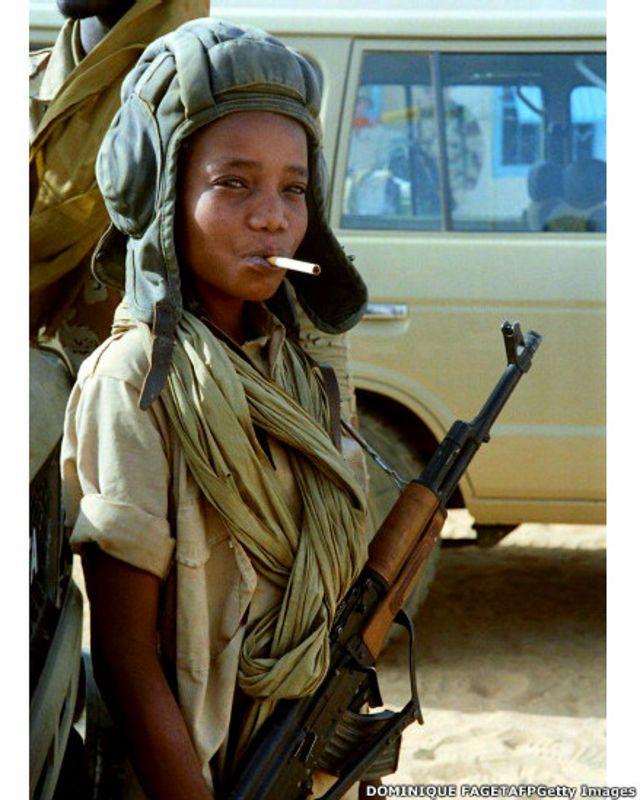 Niño soldado posa con casco, cigarrillo y Kalashnikov.