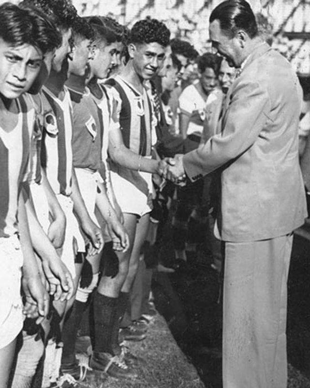 Perón saluda a un equipo de fútbol juvenil.
