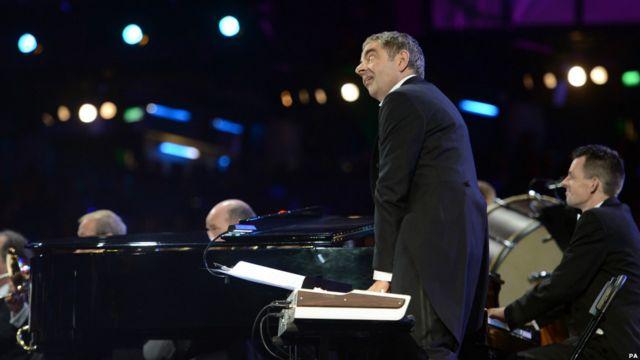 """در بخشی از مراسم افتتاحیه، در حالی که ارکستر سمفونیک لندن در حال اجرای قطعه """"ارابه های آتش بود""""، روان اتکینسون، بازیگر شخصیت مستر بین به ایفای نقش به عنوان یک نوازنده پرداخت."""