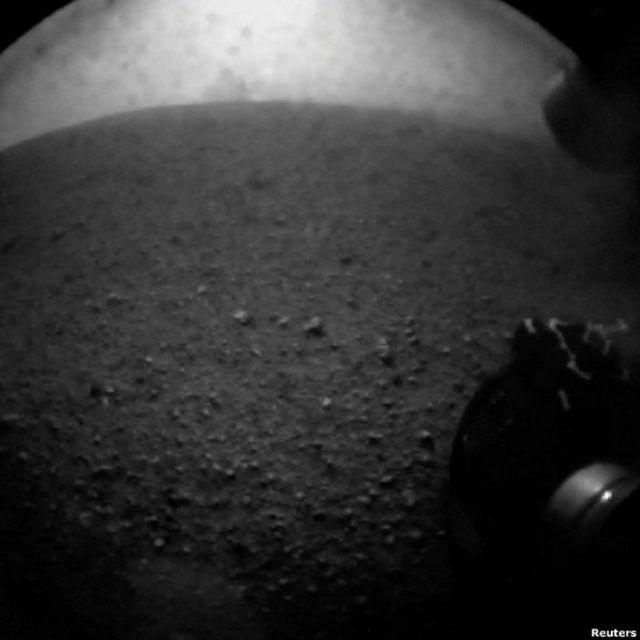 Las fotos enviadas por el Curiosity serán -por algunos días- de baja resolución. Para el fin de la semana se esperan las imágenes a color y de mejor calidad, cuando se despliegue el mástil del robot, equipado con una cámara de alta resolución.
