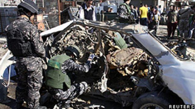 Policiais iraquianos examinam os restos de um carro-bomba no bairro Cidade Sadr, em Bagdá (Reuters)
