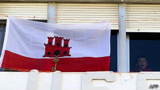 Niño al lado de una bandera gibraltareña