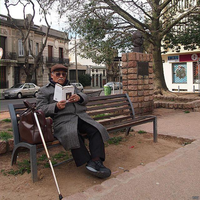 Un señor sentado cerca del monumento a Salvador Allende en Uruguay