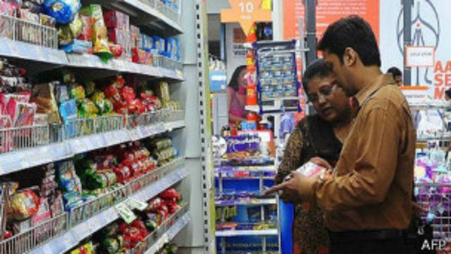 compradores revisan la etiqueta de productos en un supermercado