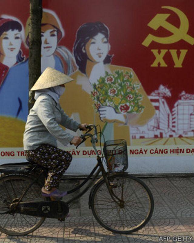 Một phụ nữ đạp xe qua áp phích ở Hà Nội hồi tháng Ba năm 2013