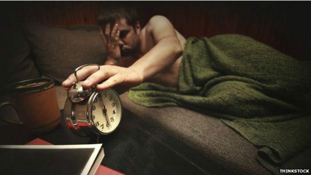 Hombre soñoliento y despertador