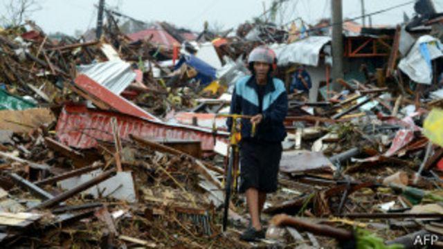 Мужчина с велосипедом на месте разрушенного дома