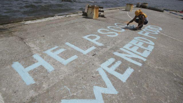 Un sobreviviente escribe un mensaje de socorro en el puerto