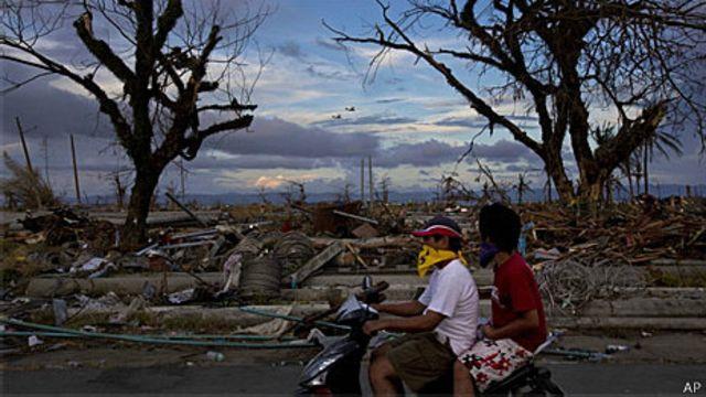 Moradores de Tacloban passam pelas ruínas da cidade destruída pelo tufão Hayan (AP)