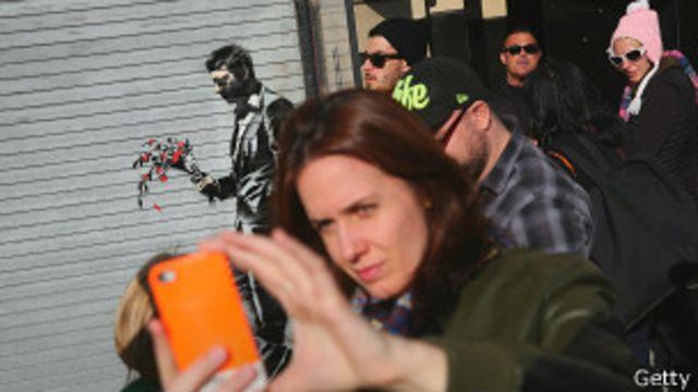 Женщина фотографирует себя на камеру смартфона в Нью-Йорке