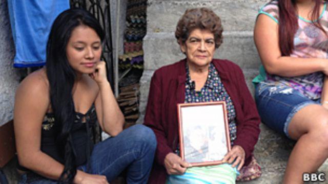 Franquelina Guerra con sus nietas en el barrio Pablo Escobar. En las rodillas, una foto de Pablo Escobar.