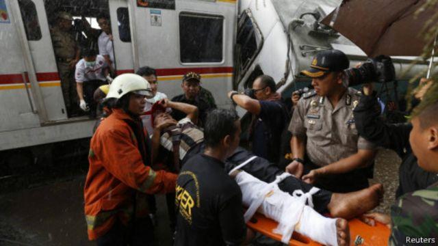Petugas menyelamatkan korban luka-luka dari gerbong komuter line.