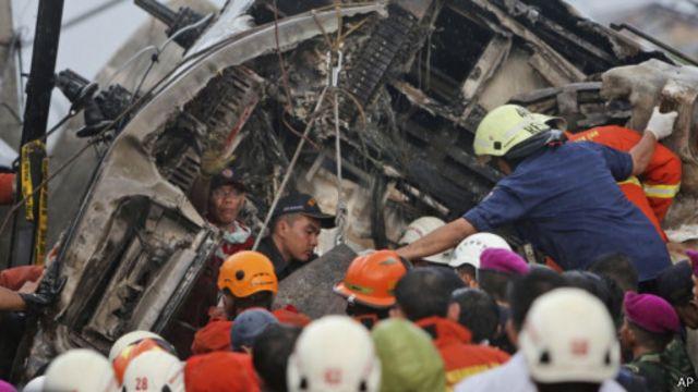 Petugas berupaya menolong korban selamat dari gerbong komuter line.