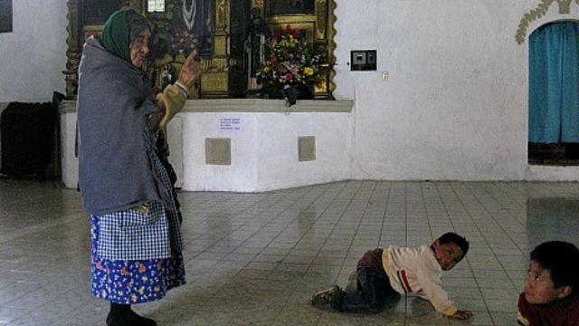 La anciana cuidadora advierte a los niños que dejen de hacer bulla.