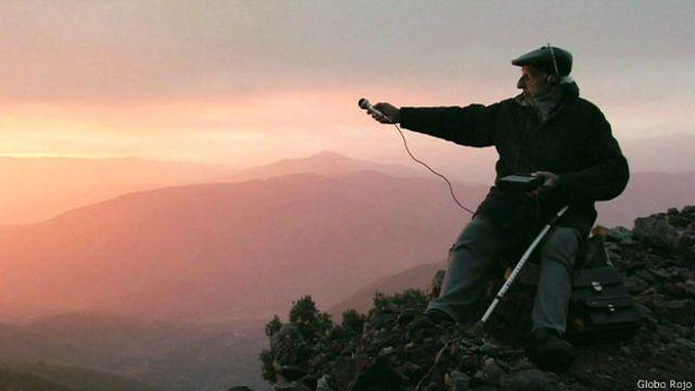 Anciano en la montaña con un micrófono
