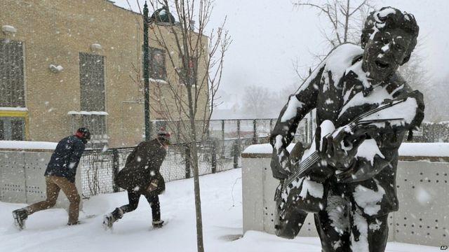 Dos personas corren por las calles de San Luis, bajo una nevada.