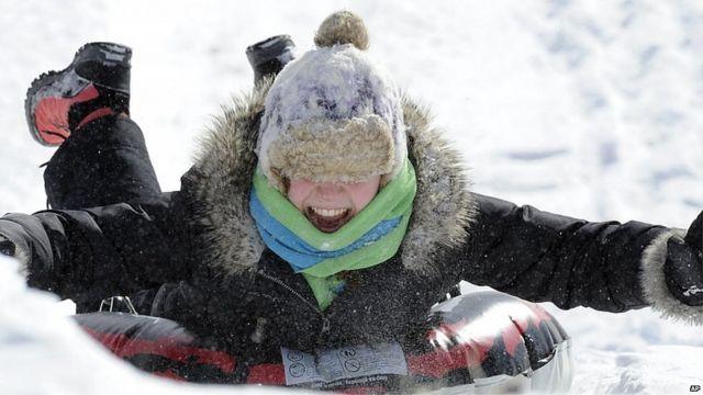 Una niña se lanza por la nieve en un trineo, en Pensilvania.