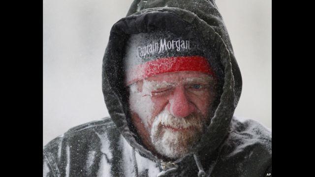 Allan Umscheid, en Kansas, sufre el viento mientras intenta quitar la nieve de su propiedad.