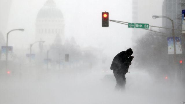 Una persona intenta cruzar la calle en una tormenta de nieve en San Luis, Misuri, EE.UU.