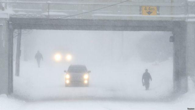 Peatones y vehículos avanzan en medio de un temporal de nieve en Halifax, Nueva Escocia, Canadá.