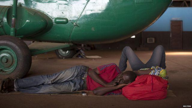 Jeudi, des hommes se reposent près d'un hélicoptère militaire dans l'aéroport de Bangui. L'aéroport sert de refuge aux musulmans fuyant les attaques en représaille. 1600 soldats français ont été envoyés en Centrafrique pour appuyer les 4000 soldats présents dans le cadre de la force panafricaine.