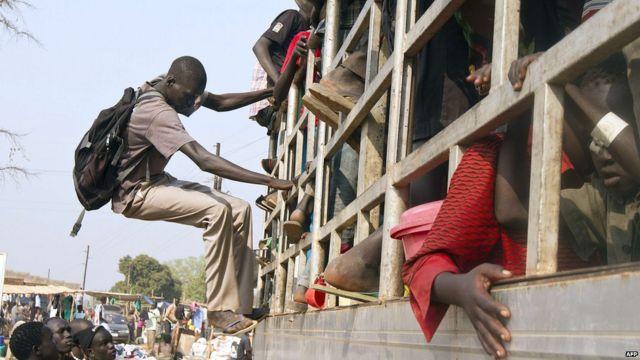 Le même  jour au nord de l'Ouganda, des réfugiés sud-soudanais montent dans un camion avant d'être transférés vers un centre de transit à Adjumani, puis vers un camp de déplacés. Selon l'ONU, quelque 60900 Sud-Soudanais ont fui vers l'Ouganda depuis le début des combats à la mi-décembre.