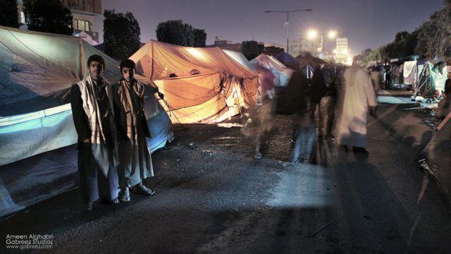 امين الغابري مصور يمني محترف التقط بكاميرته مشاهد من الثورة اليمنية. شابان يقفان أمام خيمة في ميدان التغيير بصنعاء 2011
