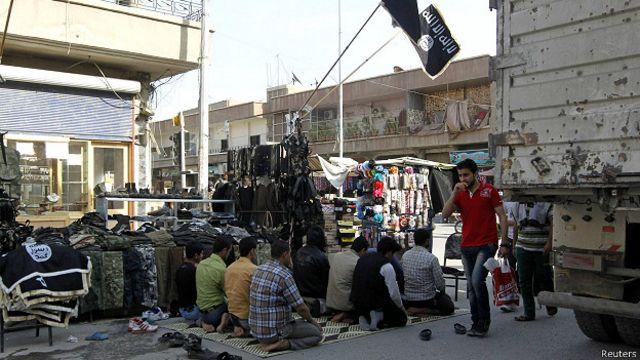 Сирийцы молятся в Ракке на фоне джихадистских флагов