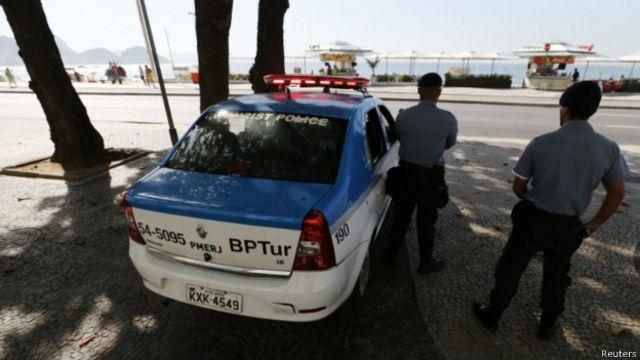 Dos policías vigilando junto a un patrullero, frente a una playa de Río de Janeiro.
