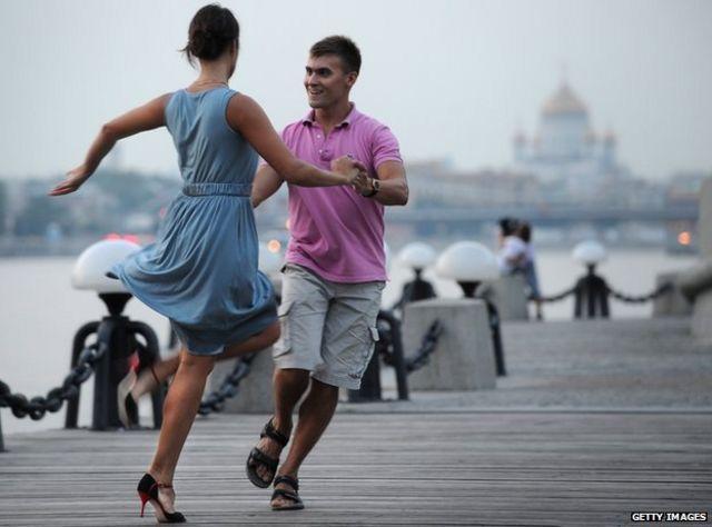 Танцующая на берегу Москва-реки пара